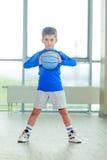 Niño pequeño que juega la bola y la forma azules del baloncesto Foto de archivo