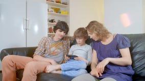Niño pequeño que juega la videoconsola portátil la familia que lo mira con interés metrajes