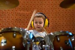 Niño pequeño que juega los tambores con los auriculares de la protección Imagen de archivo libre de regalías