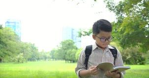 Niño pequeño que lee el libro en el camino a la escuela metrajes