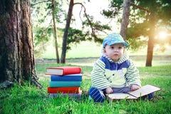 Niño pequeño que lee un libro mientras que se sienta en la hierba verde en parque Pila de libros de texto multicolores y de bebé  Foto de archivo