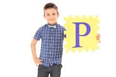 Niño pequeño que lleva a cabo el pedazo amarillo de un rompecabezas Imágenes de archivo libres de regalías