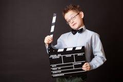 Niño pequeño que lleva a cabo el tablero de chapaleta en manos. Imagen de archivo libre de regalías