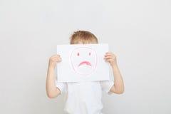 Niño pequeño que lleva a cabo la mascarilla triste Imagen de archivo
