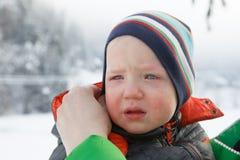 Niño pequeño que llora, su madre que intenta consolarlo foto de archivo
