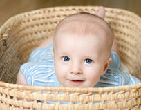 Niño pequeño que miente en cesta de mimbre Foto de archivo libre de regalías