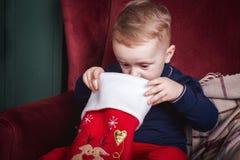 Niño pequeño que mira dentro de una media de la Navidad foto de archivo libre de regalías