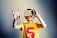 Niño pequeño que mira en gafas de un VR y que gesticula con sus manos en fondo gris foto de archivo libre de regalías