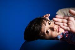 Niño pequeño que mira en la cámara con una mano en frente Fotos de archivo libres de regalías