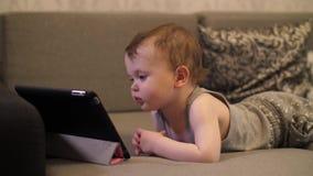Niño pequeño que mira en la tableta almacen de metraje de vídeo