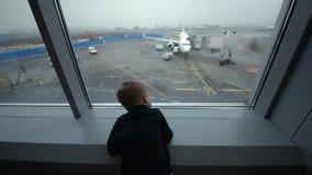 Niño pequeño que mira hacia fuera la ventana el aeropuerto almacen de metraje de vídeo