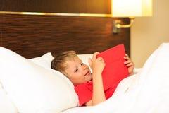 Niño pequeño que mira la almohadilla táctil que miente en cama de Imagen de archivo libre de regalías