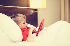 Niño pequeño que mira la almohadilla táctil que miente en cama de Foto de archivo