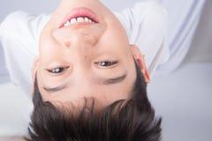 Niño pequeño que mira para arriba con la sonrisa en el fondo blanco Fotografía de archivo libre de regalías
