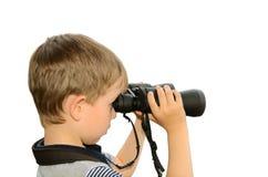 Niño pequeño que mira a través de los prismáticos el mar vista lateral, aislante Fotos de archivo