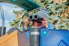Niño pequeño que mira a través de los prismáticos en una diapositiva el patio Fotografía de archivo libre de regalías