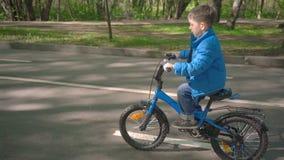 Niño pequeño que monta la bici azul en parque de la ciudad metrajes