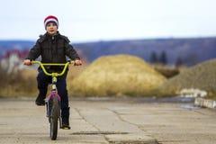 Niño pequeño que monta su bicicleta en parque al aire libre Fotos de archivo