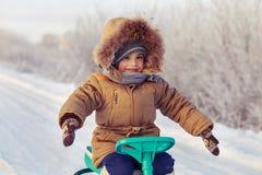 Niño pequeño que monta su camino nevado del invierno de la moto de nieve de los niños Imágenes de archivo libres de regalías