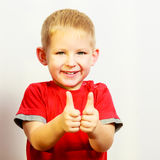 Niño pequeño que muestra el pulgar encima del gesto de la muestra de la mano del éxito Imagen de archivo
