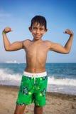 Niño pequeño que muestra los músculos en la playa Fotos de archivo libres de regalías