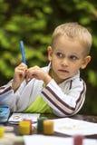 Niño pequeño que piensa con un lápiz mientras que dibuja Educación Imagen de archivo libre de regalías