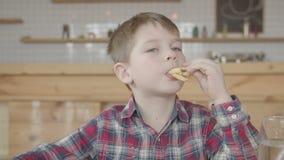 Niño pequeño que pone las patatas fritas en boca en café metrajes