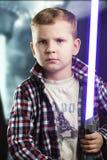 Niño pequeño que presenta con una espada del laser Foto de archivo