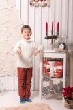 Niño pequeño que presenta en interior de la Navidad Imágenes de archivo libres de regalías