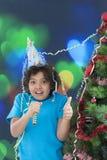 Niño pequeño que ríe en víspera del ` s del Año Nuevo, el sombrero brillante que lleva y el cuerno que sopla, Imagenes de archivo