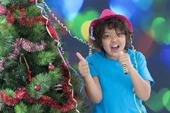 Niño pequeño que ríe en víspera del ` s del Año Nuevo, el sombrero brillante que lleva y el cuerno que sopla, Imagen de archivo