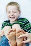 Niño pequeño que ríe los pies felices que cosquillean Fotos de archivo