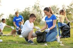 Niño pequeño que recoge basura con el voluntario foto de archivo