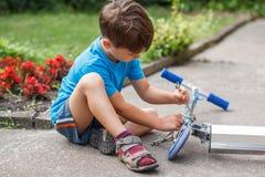 Niño pequeño que repara la vespa Foto de archivo libre de regalías