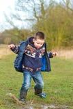 Niño pequeño que salpica en un charco en el campo Imágenes de archivo libres de regalías