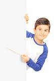 Niño pequeño que señala en un panel en blanco con el palillo Fotos de archivo libres de regalías