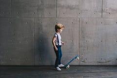Niño pequeño que se coloca con un monopatín en una pared Imagenes de archivo