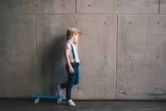 Niño pequeño que se coloca con un monopatín en una pared Foto de archivo libre de regalías
