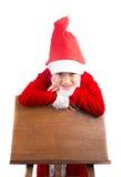 Niño pequeño que se coloca sobre tablero de madera de la estación en blanco Foto de archivo