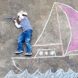 Niño pequeño que se divierte con el dibujo de la imagen de la nave con tiza Fotos de archivo