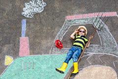 Niño pequeño que se divierte con el dibujo de la imagen del tractor con tiza Fotos de archivo libres de regalías