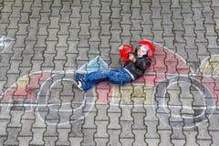 Niño pequeño que se divierte con el dibujo del coche de carreras con tizas Foto de archivo libre de regalías