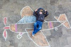 Niño pequeño que se divierte con la imagen del aeroplano Foto de archivo libre de regalías