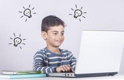 Niño pequeño que se divierte usando un ordenador portátil Fotos de archivo