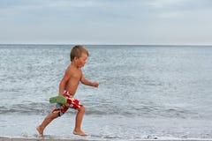 Niño pequeño que se ejecuta en la costa Imagen de archivo libre de regalías