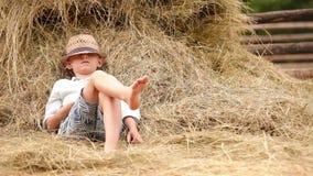 Niño pequeño que se relaja cerca de la pila de heno metrajes