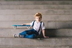 Niño pequeño que se sienta con un monopatín en las escaleras Fotos de archivo libres de regalías