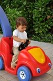 Niño pequeño que se sienta en coche del juguete Imagen de archivo libre de regalías