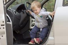 Niño pequeño que se sienta en el coche y que va a salir fotos de archivo