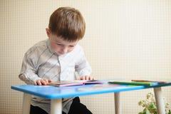 Niño pequeño que se sienta en el escritorio y que lee un libro Fotos de archivo